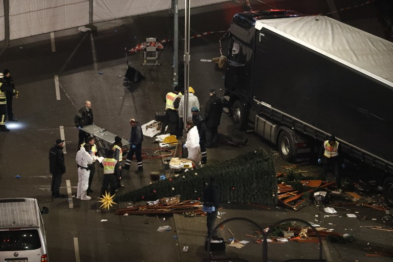 Authorites inspect the scene after a truck sped into a Christmas market in Berlin, on December 19, 2016, killing at least nine people and injuring dozens more. Ambulances and heavily armed officers rushed to the area after the driver drove up the pavement of the market in a square popular with tourists, in scenes reminiscent of the deadly truck attack in the French city of Nice last July. / AFP PHOTO / Odd ANDERSEN